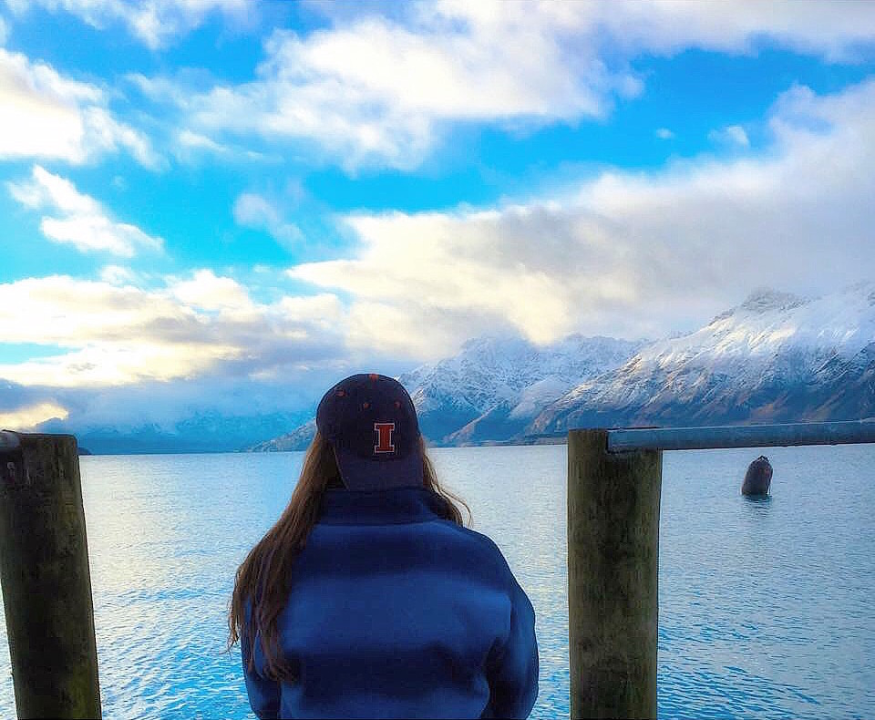 Emma in UofI hat overlooks sea & mountains in New Zealand